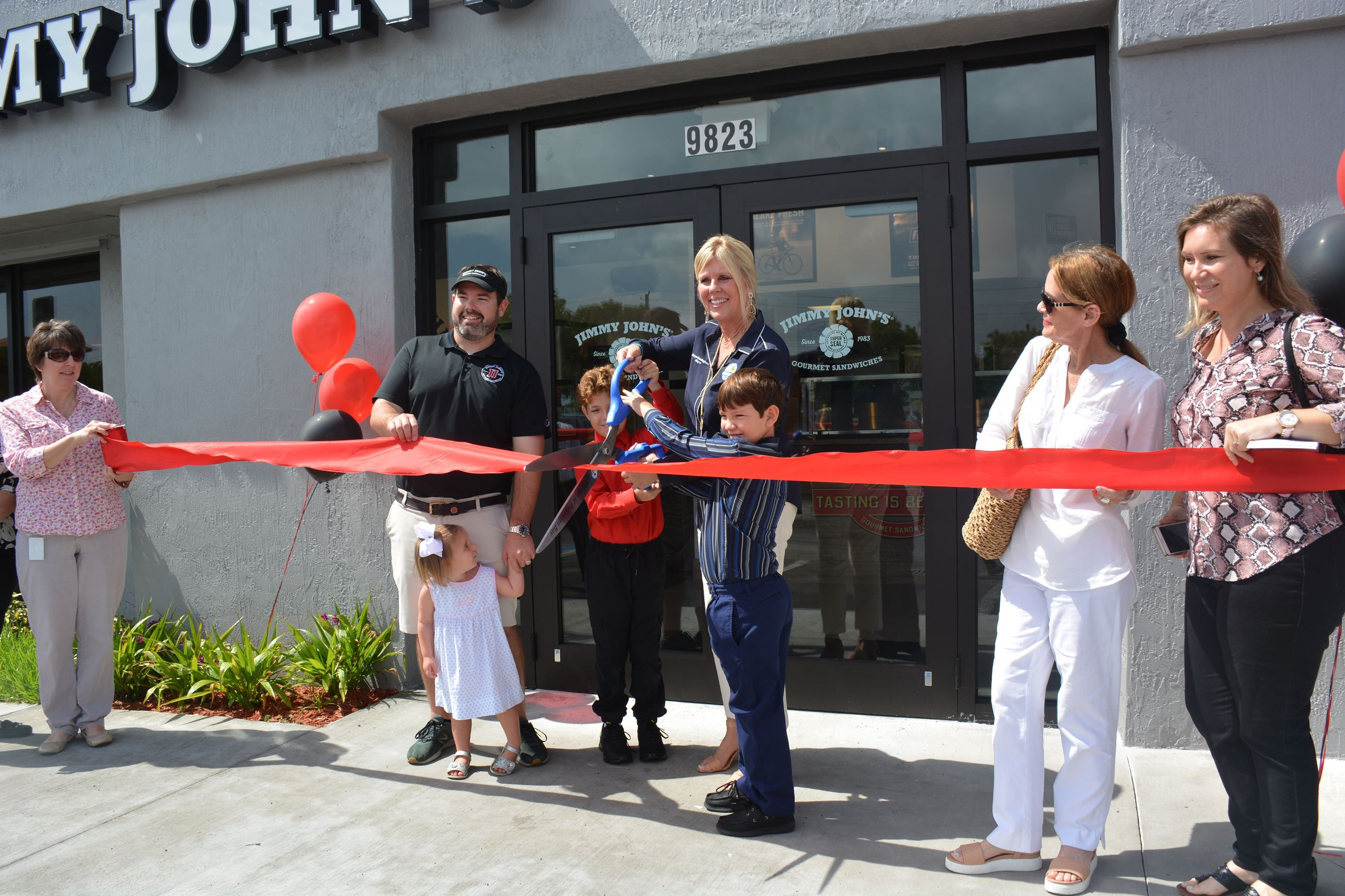 Mayor Cunningham and Franchisee Wade Copeland gather with others to cut the ribbon at the new Jimmy