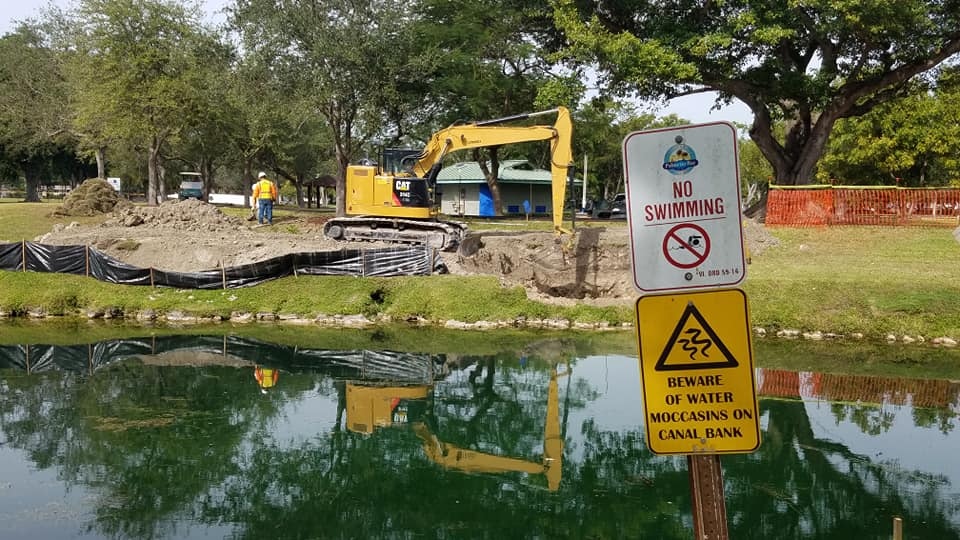 coral reef park footbridge construction.  Shows equipment, canal and temporary fencing.